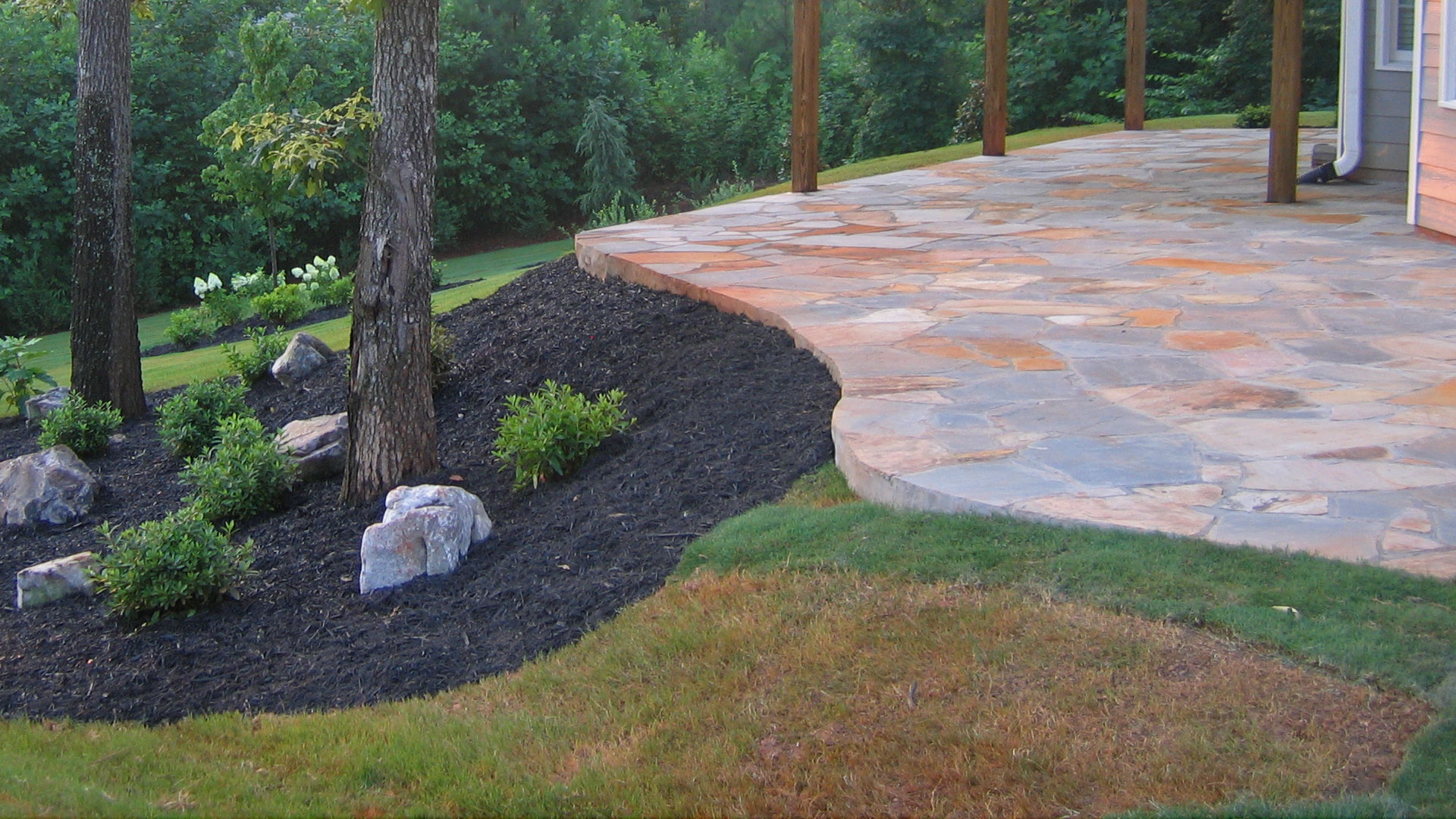 Flagstone patio constructed in the backyard of a home in Smyrna with softscaping.