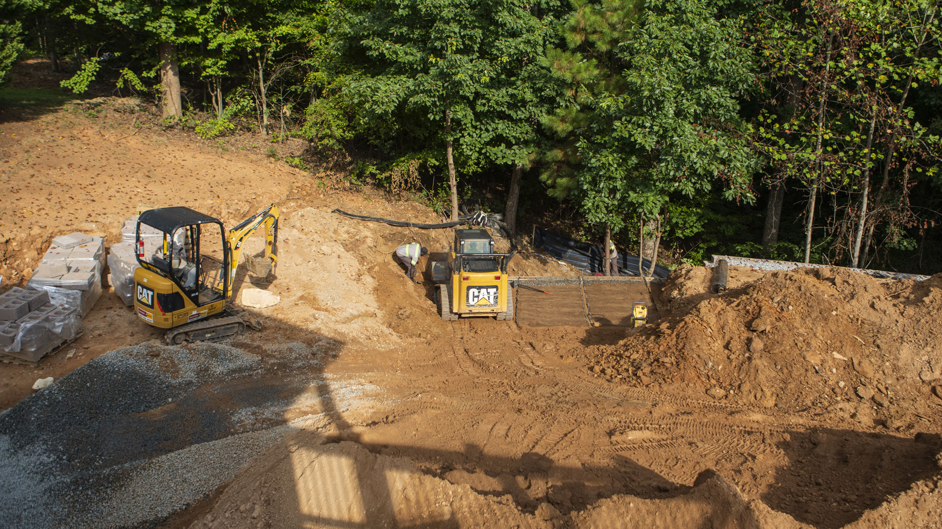 Our team grading a property, preparing for a new retaining wall, fire pit, and patio.
