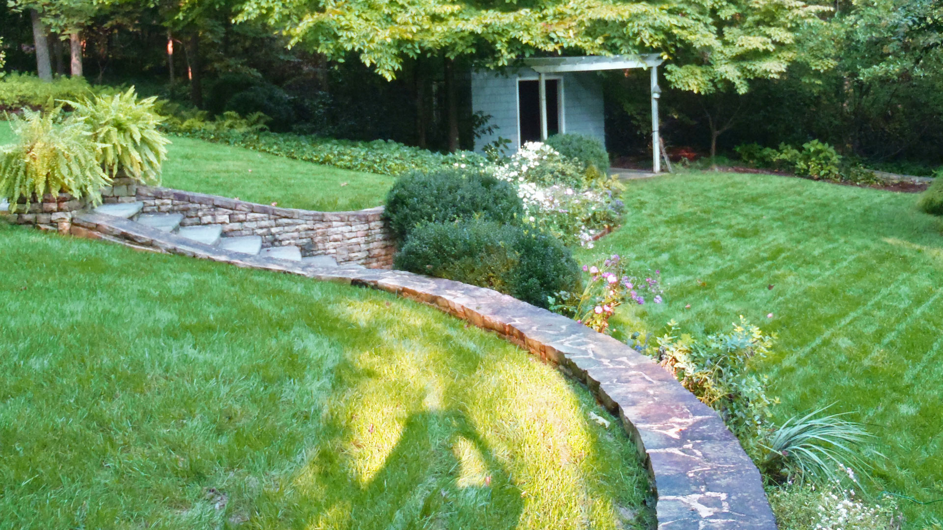 Backyard with hardscaping, steps, retaining wall, and mowed lawn.