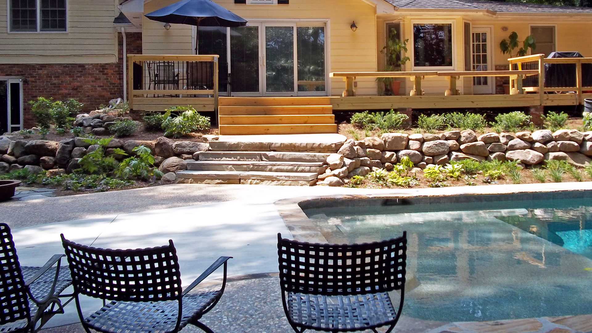 Rock retaining wall with landscaping around a pool at a home in Mableton, GA.