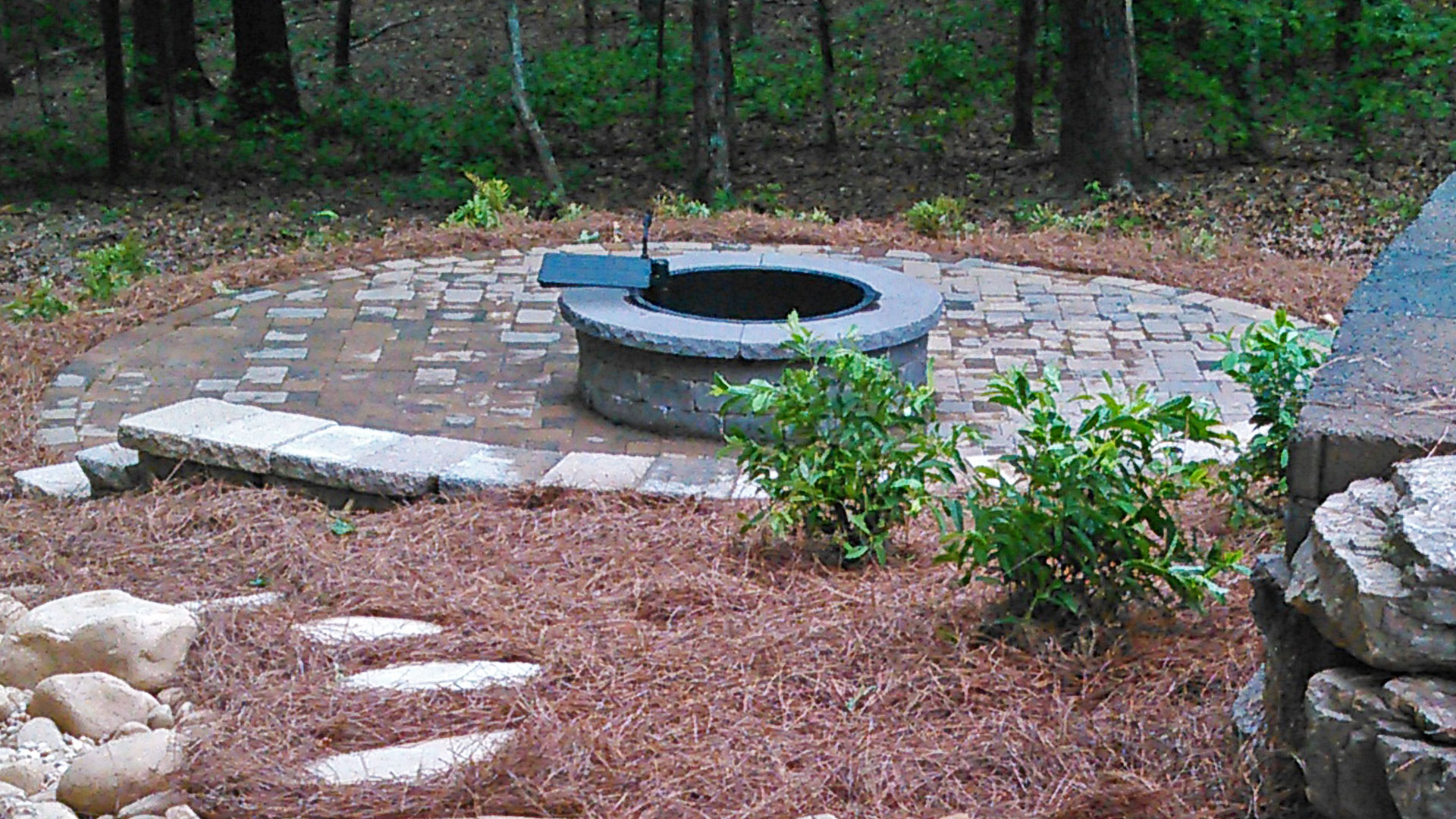 A round fire pit with a paver patio, seating wall, and retaining wall.