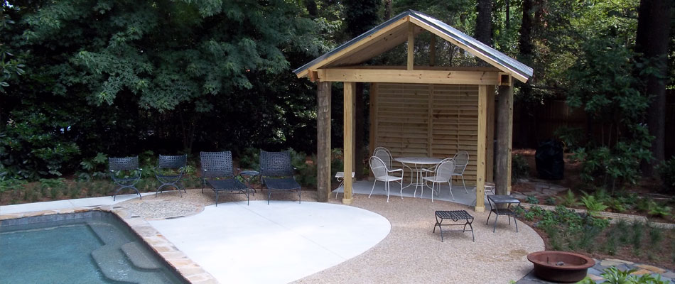 Decorative concrete around a pool with a pavilion and softscaping