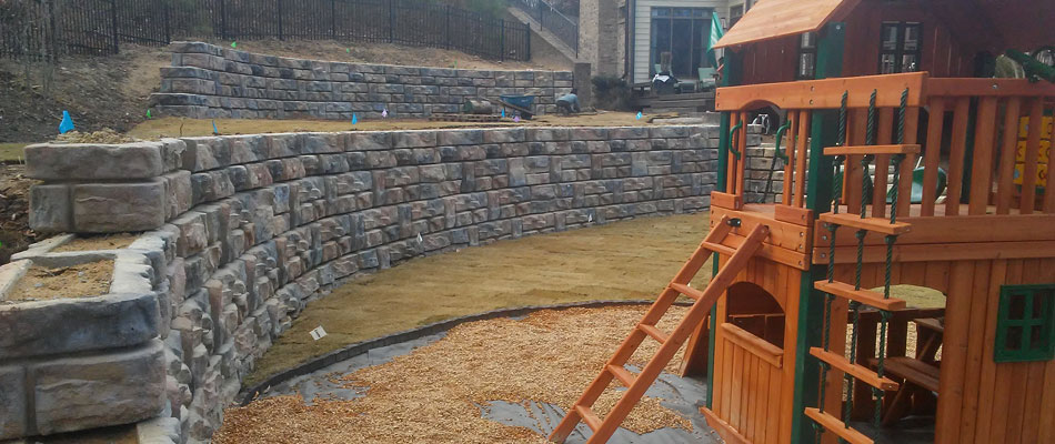 Two retaining walls to control soil erosion around a playground in Buckhead, GA.