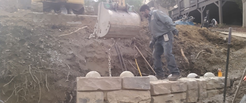Preparing a property for a new retaining wall and retaining wall materials.